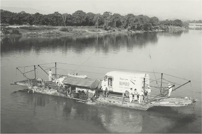 Foto antigua mostrando un camión de Bimbo cruzando un canal en una gran lancha